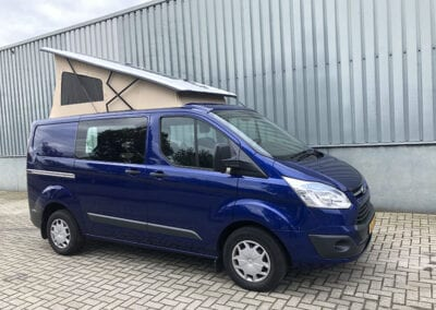 CMC Nederland - Blauwe Ford Transit Custom - Voorkant